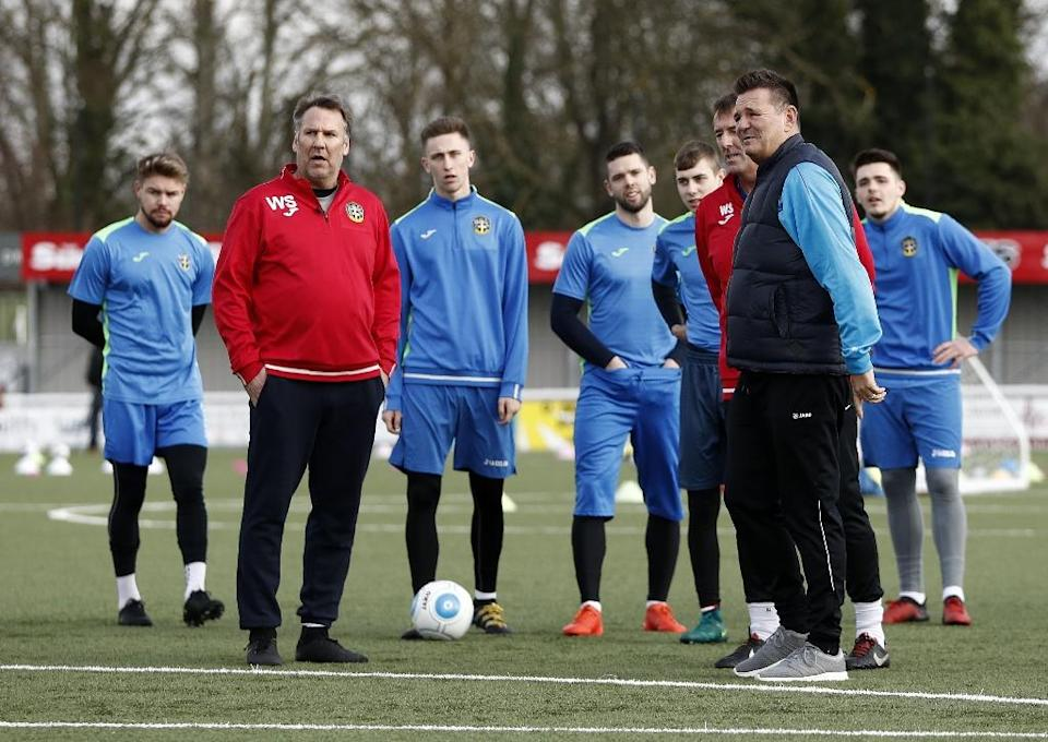 Sutton United's English manager Paul Doswell (R) and former Arsenal player Paul Merson (2L) stand on the pitch with the players during a team training session in Sutton, sout-west London, on February 16, 2017 (AFP Photo/ADRIAN DENNIS)