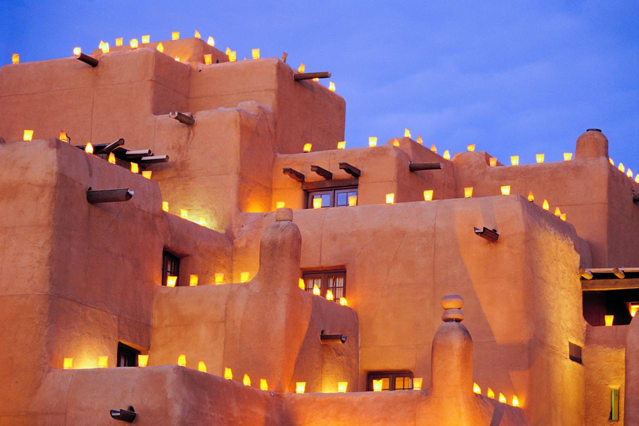 """Proving that holiday lights don't need to be LED to be dazzling, Santa Fe's annual <a href=""""https://www.farolitowalk.com/"""">Canyon Road Farolito Walk</a> consists of farolitos (paper bags filled with sand and topped with a votive candle) lining the streets and walls of adobe buildings. You'll also see luminarias (small wood bonfires) spaced along the street. The walk takes place at dusk on Christmas Eve and lasts until late evening—show up early if you want any chance of nabbing a parking spot."""