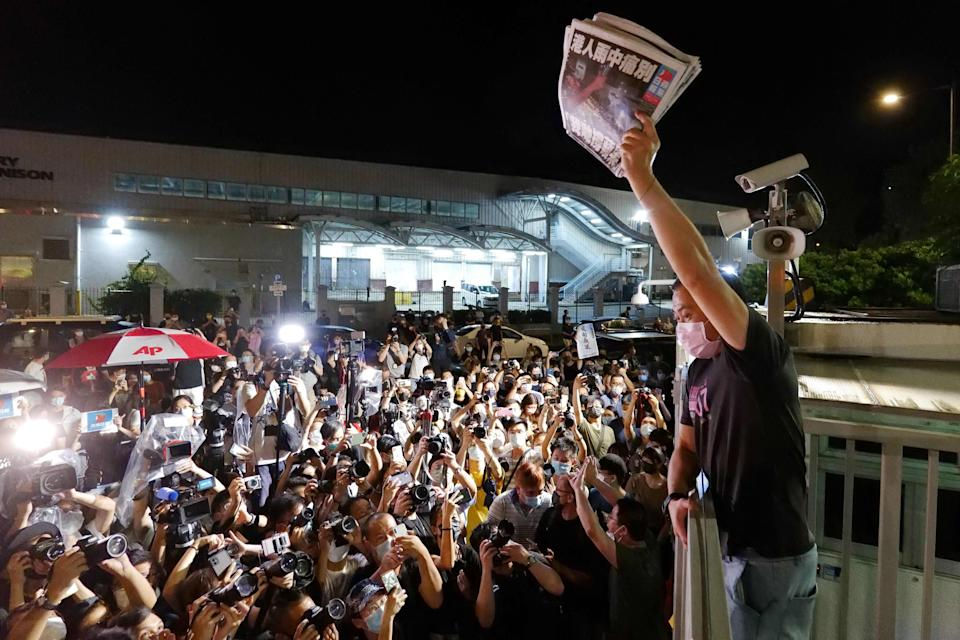 An Apple Daily journalist holds freshly-printed copies of the newspaper's last edition to be distributed to supporters gathered outside their office in Hong Kong early on 24 June (AFP via Getty Images)