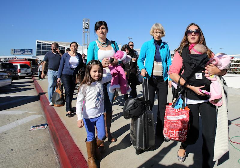 Passengers evacuate the Los Angeles International Airport on Friday Nov. 1, 2013, after shots were fired prompting authorities to evacuate a terminal and stop flights headed for the city from taking off from other airports. (AP Photo/Ringo H.W. Chiu)