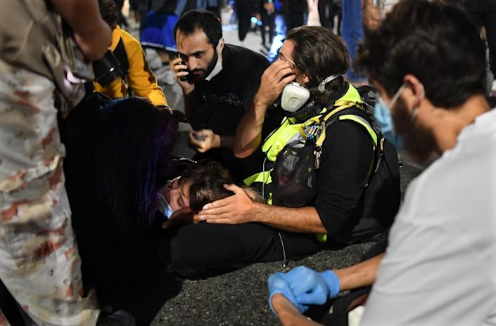 Paramedics treat a protester who was run over by a car on Sunset Boulevard on Thursday night.