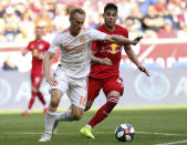 FILE - In this May 19, 2019, file photo, Atlanta United midfielder Jeff Larentowicz, left, keeps the ball away from New York Red Bulls forward Brian White during the first half of an MLS soccer match in Harrison, N.J. Larentowicz has retired after a 16-year career in Major League Soccer that included more than 400 appearances and championships in Colorado and Atlanta. (AP Photo/Steve Luciano, File)