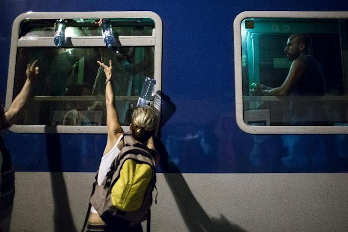 A volunteer distributes water to migrants on a train from Budapest to Munich at the Austrian - Hungarian border in Hegyeshalom on August 31, 2015 (AFP Photo/Vladimir Simicek)