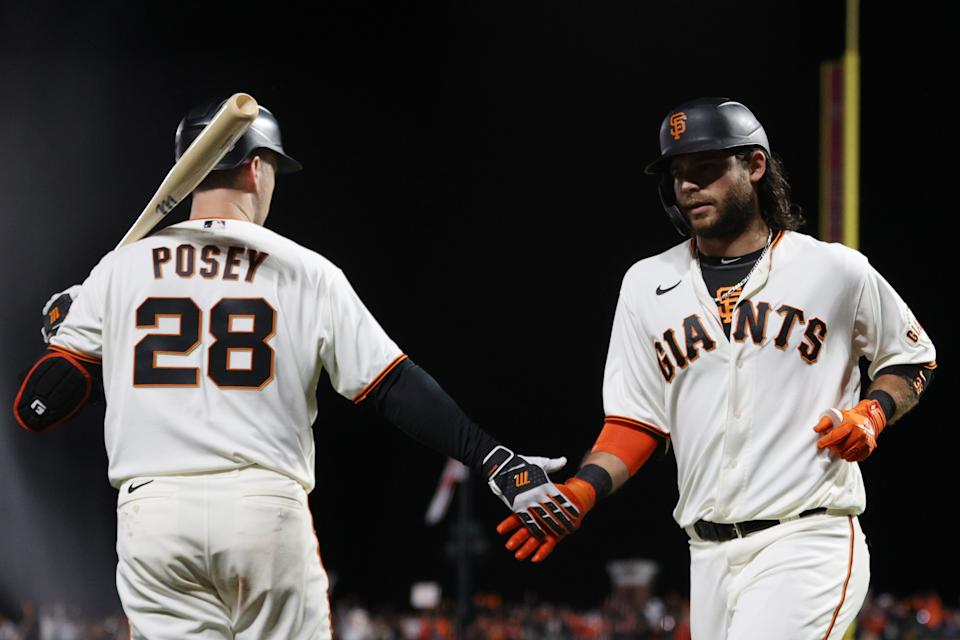 Buster Posey and Brandon Crawford clap hands as the Giants defeat the Dodgers.