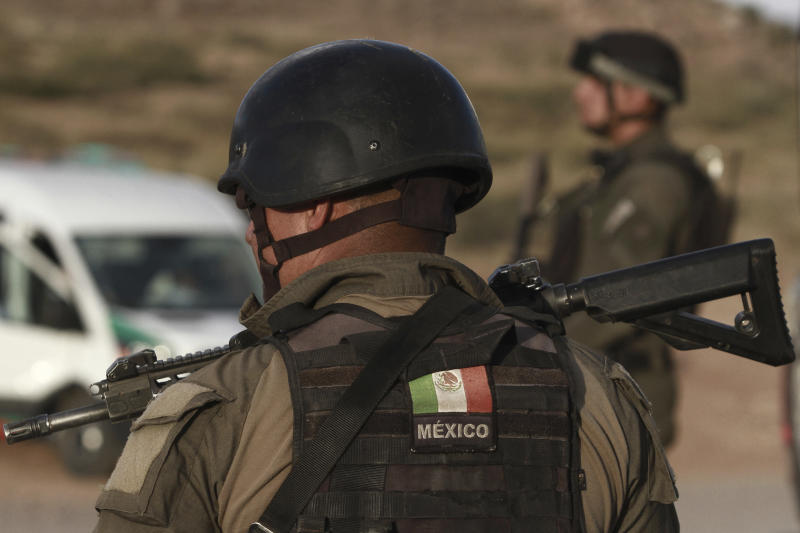 Chihuahua state police officers man a checkpoint in Janos, Chihuahua state, northern Mexico, Tuesday, Nov. 5, 2019. Drug cartel gunmen ambushed three SUVs along a dirt road, slaughtering six children and three women, all U.S. citizens living in northern Mexico, in a grisly attack that left one vehicle a burned-out, bullet-riddled hulk, authorities said Tuesday. (AP Photo/Christian Chavez)