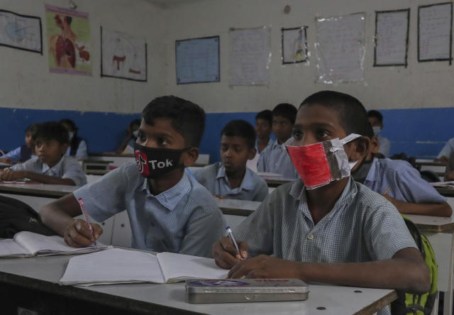 Indian students wear masks and listen to a teacher at a government school in Hyderabad, India. (AP)