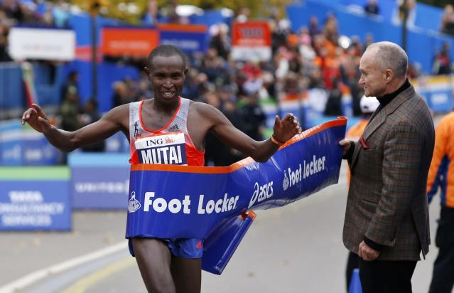 Geoffrey Mutai of Kenya (L) crosses the finish line to win the men's division of the New York City Marathon in New York, November 3, 2013. New York City Police Commissioner Ray Kelly is on right. Mutai broke away with about four miles to go to win the New York City Marathon in blustery, chilly conditions on Sunday. REUTERS/Mike Segar (UNITED STATES - Tags: SPORT ATHLETICS)