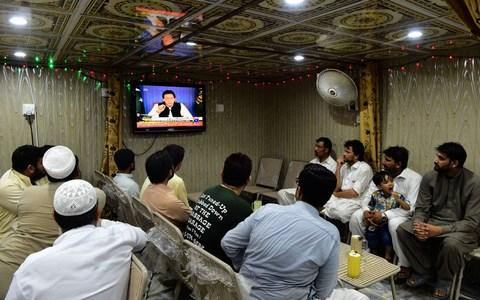 Pakistani men watch a television broadcasting Imran Khan's speech - Credit: ABDUL MAJEED/AFP