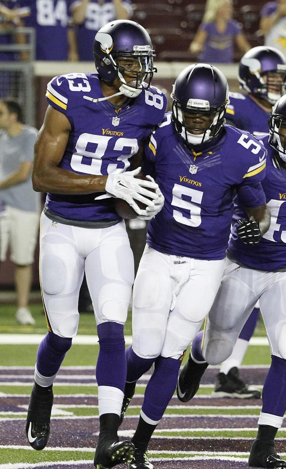 Minnesota Vikings wide receiver Rodney Smith, left, celebrates with quarterback Teddy Bridgewater (5) after catching a 2-yard touchdown pass during the second half of an NFL preseason football game against the Arizona Cardinals, Saturday, Aug. 16, 2014, in Minneapolis. The Vikings won 30-28. (AP Photo/Ann Heisenfelt)