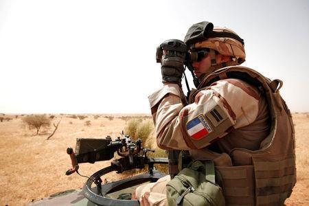 FILE PHOTO: A French soldier from the 12th armoured regiment uses his binoculars from an armoured vehicle during the regional anti-insurgent Operation Barkhane in Inaloglog, Mali, October 17, 2017. REUTERS/Benoit Tessier/File Photo