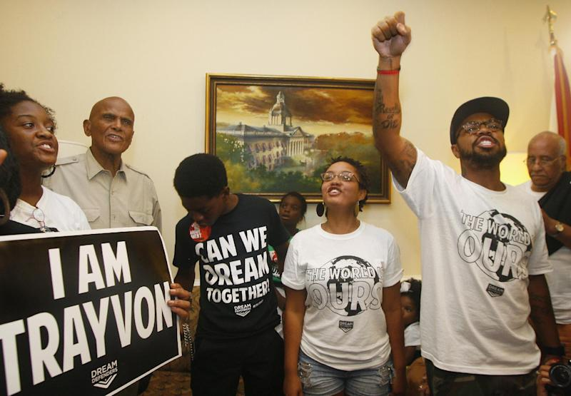 At left, American singer, songwriter, actor and social activist Harry Belafonte, Jr. listens as Dream Defenders Executive Director Phillip Agnew, right, raises his fist as he leads a chant calling for a special session Friday, July 26, 2013 in the Capitol in Tallahassee, Fla. Dream Defenders were joined by Belafonte, Jr. as they went into their 11th day of a sit-in of Florida Gov. Rick Scott's office. The sit-in is their response to the 'not guilty' verdict in the trial of George Zimmerman, the Florida neighborhood watch volunteer who fatally shot Trayvon Martin. They are continuing to demand Scott call a special session. (AP Photo/Phil Sears)