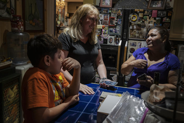 Mirna and her son, Yosemar, with Vonnette Monteith, center, in Louisville, Ky. Since Mirna does not speak English and Vonnette does not speak Spanish, they use Google Translate to communicate. (Photo: Fabio Bucciarelli for Yahoo News)