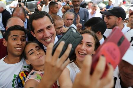 Venezuelan opposition leader Juan Guaido, who many nations have recognized as the country's rightful interim ruler, poses for a picture while attending a political rally in Caracas