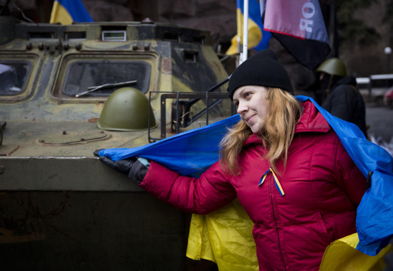 A protester poses next to an captured armored vehicle, in central Kiev, Ukraine, Saturday, Feb. 22, 2014. Protesters in the Ukrainian capital claimed full control of the city Saturday following the signing of a Western-brokered peace deal aimed at ending the nation's three-month political crisis. The nation's embattled president, Viktor Yanukovych, reportedly had fled the capital for his support base in Ukraine's Russia-leaning east. (AP Photo/Darko Bandic)