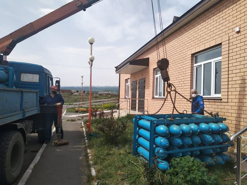Workers unload oxygen balloons outside a local hospital in Dagestan's Gurbuki village