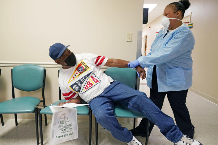 FILE - In this April 7, 2021, file photo, Wilbert Marshall, 71, left, pretends to be scared of receiving the COVID-19 vaccine from a nurse at the Aaron E. Henry Community Health Service Center in Clarksdale, Miss. Marshall, who was among a group of seniors from the Rev. S.L.A. Jones Activity Center for the Elderly who received their vaccinations, said he wanted the vaccination in order to stay safe and be able to visit with family without the constant fear of the virus. (AP Photo/Rogelio V. Solis)
