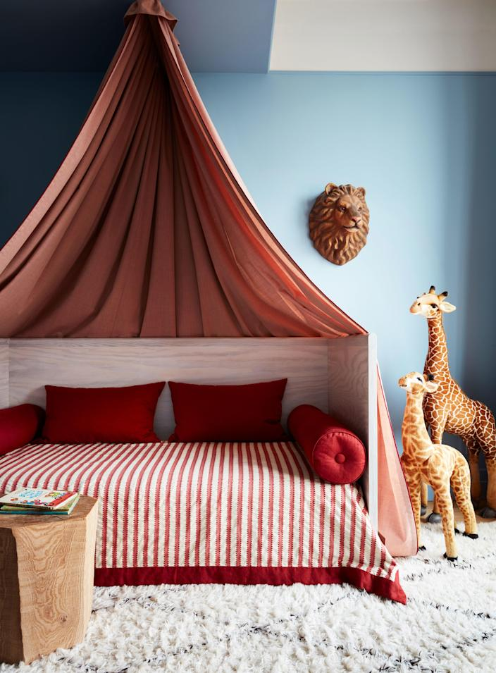 The son's room, which is painted Lulworth Blue from Farrow & Ball, has a custom canopy bed accented by a decoupage lion's head from John Derian.