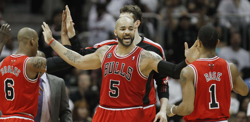 Chicago Bulls power forward Carlos Boozer (5) reacts to a goal with teammates Keith Bogans, left, and  Derrick Rose (1)  in the third quarter of Game 6 of an NBA basketball Eastern Conference semifinal playoff series against the Atlanta Hawks, Thursday, May 12, 2011, in Atlanta. (AP Photo/John Bazemore)