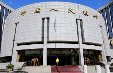 FILE PHOTO: A woman walks out of the headquarters of PBOC in Beijing