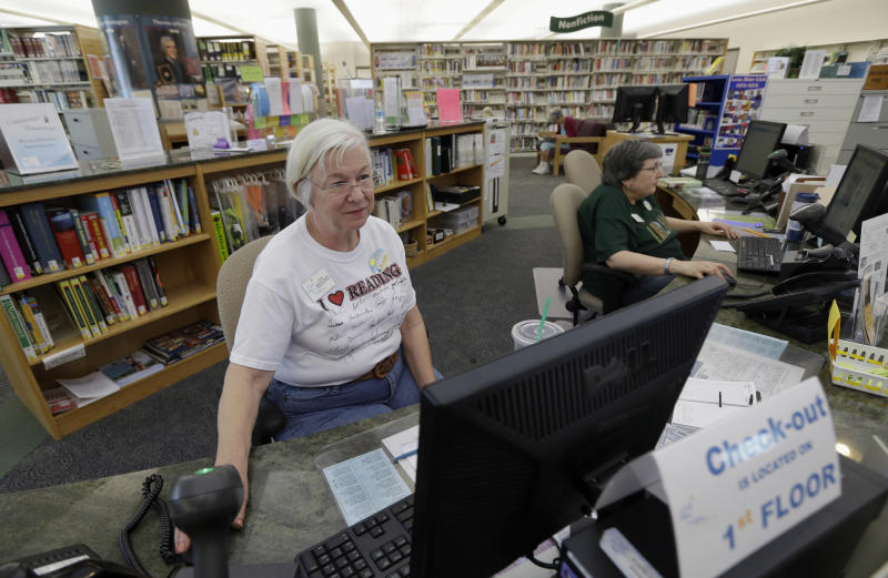 Librarian Joan Limbert, left, works at her station inside the Barbara Bush Branch Library Friday, June 28, 2013, in Spring, Texas. The nation's librarians will be recruited to help people get signed up for insurance under President Barack Obama's health care overhaul. Up to 17,000 U.S. libraries will be part of the effort to get information and crucial computer time to the millions of uninsured Americans who need to get coverage under the law. The undertaking will be announced Sunday in Chicago at the annual conference of the American Library Association, according to federal officials who released the information early to The Associated Press. (AP Photo/David J. Phillip)