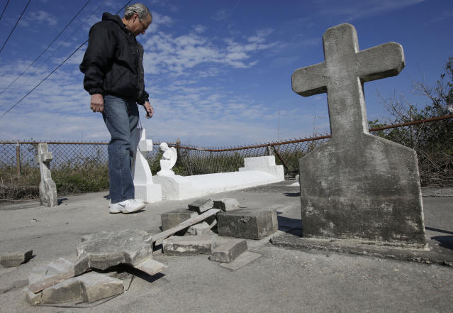 In this Dec. 29, 2012 photo, South Lafourche Levee District General Manager Windell Curole, who also serves on the state's Coastal Protection and Restoration Authority, walks through his small family cemetery which sits along the bayou near Leeville, La. Some 11 cemeteries in Jefferson Parish have repeatedly flooded since Katrina, and in Lafourche, Terrebonne and Plaquemines parishes, more than a dozen others have succumbed to tidal surges. Curole said saltwater from the Gulf is causing a crippling subsidence problem. (AP Photo/Dave Martin)