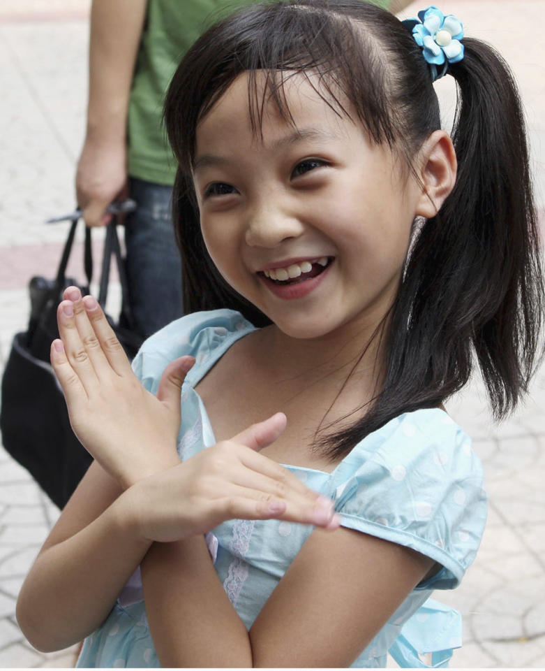 "In this photo released by China's Xinhua News Agency, Lin Miaoke, a nine-year-old Chinese girl who performed at the opening ceremony of the Beijing Olympics on the day before, returns to the Xizhongjie Primary School of Dongcheng District in Beijing on Saturday, Aug. 9, 2008. A 7-year-old Chinese girl's face was ""not suitable"" for the Olympics opening ceremony, so Lin lip-synched ""Ode to the Motherland"", the latest example of the lengths Beijing took for a perfect start to the Summer Games. (AP Photo/Xinhua, Zhou Liang)"