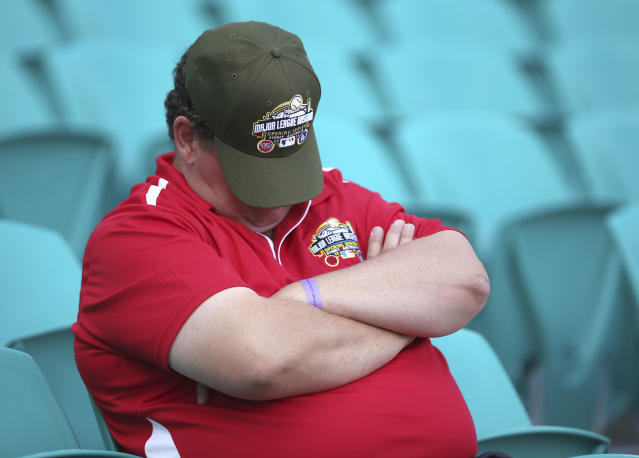 A member of the ground crew takes a break before teams train at the Sydney Cricket ground in Sydney, Friday, March 21, 2014. Major League Baseball will open their season Saturday in Sydney with the Los Angeles Dodgers taking on the Arizona Diamondbacks. (AP Photo/Rick Rycroft)