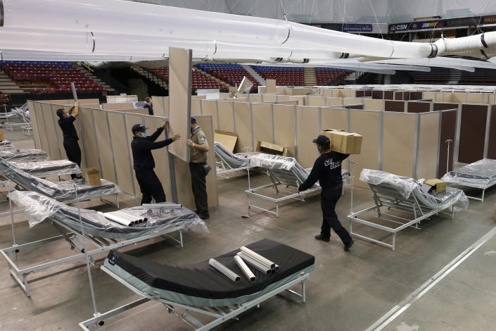 FILE— In this April 18, 2020 file photo partitions are installed between beds as work is performed to turn the Sleep Train Arena into a 400 bed emergency field hospital to help deal with the coronavirus, in Sacramento, Calif. California spent nearly $200 million to set up, operate and staff alternate care sites that ultimately provided little help when the state's worst coronavirus surge spiraled out of control last winter, forcing exhausted hospital workers to treat patients in tents and cafeterias. (AP Photo/Rich Pedroncelli, File)