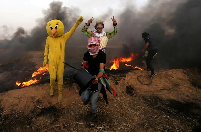 <p>Palestinians wearing costumes are seen at the clashes scene at Israel-Gaza border in the southern Gaza Strip, April 5, 2018. (Photo: Ibraheem Abu Mustafa/Reuters) </p>