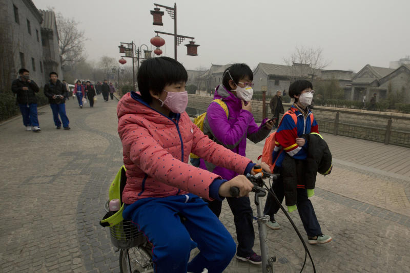 FILE - In this Tuesday, Feb. 25, 2014 file photo, children wearing masks walk home after school in Beijing, China. Air pollution kills about 7 million people worldwide every year according to a new report from the World Health Organization published Tuesday, March 25, 2014. The agency said air pollution triggers about 1 in 8 deaths and has now become the single biggest environmental health risk, ahead of other dangers like second-hand smoke. (AP Photo/Ng Han Guan, File)