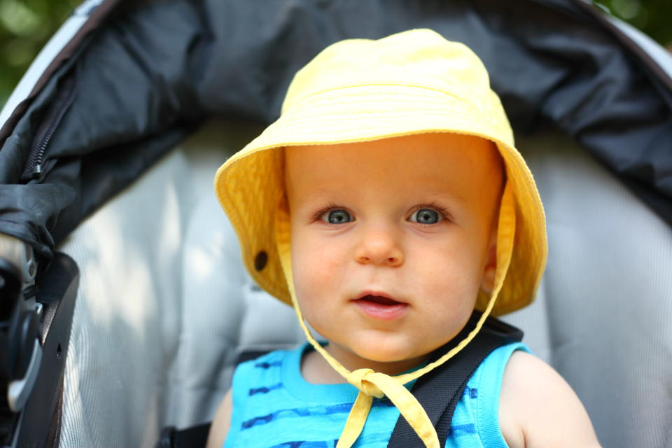 Experts suggest dressing babies in light layers and a hat for sun protection when outdoors. Image via Getty Images.