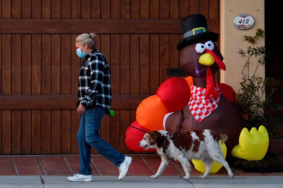 A pedestrian wearing a face mask walks her dog past an inflatable turkey ahead of the Thanksgiving holiday during increased COVID-19 restrictions in Manhattan Beach, California, November 21, 2020.