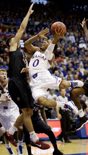Kansas' Frank Mason (0) puts up a shot under pressure from San Diego State's JJ O'Brien during the first half of an NCAA college basketball game Sunday, Jan. 5, 2014, in Lawrence, Kan. (AP Photo/Charlie Riedel)