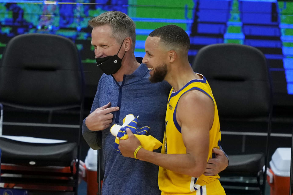 Golden State Warriors coach Steve Kerr and guard Stephen Curry laugh as they walk off the court after a 117-113 victory against the Sacramento Kings in an NBA basketball game on Sunday, April 25, 2021, in San Francisco. (AP Photo/Tony Avelar)