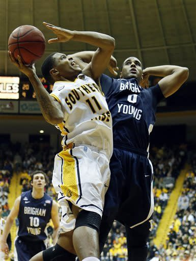 Southern Mississippi forward Daveon Boardingham (11) attempts a layup past BYU forward Brandon Davies (0) in the first half of their NIT college basketball game in Hattiesburg, Miss., Wednesday, March 27, 2013. (AP Photo/Rogelio V. Solis)
