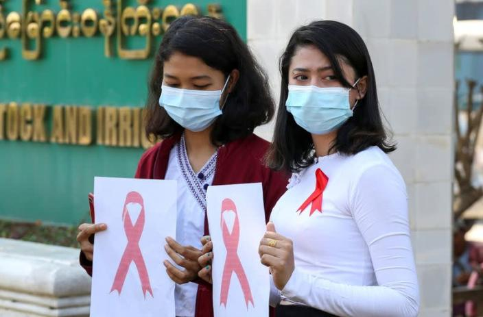 Government staff wearing red ribbons pose during a protest against the coup that ousted elected leader Aung San Suu Kyi in Naypyitaw