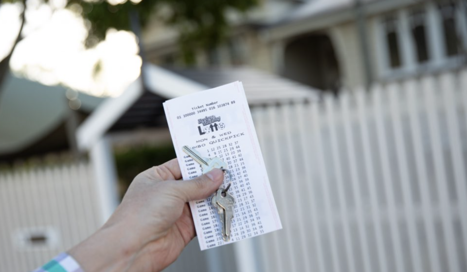 A man holding a lotto ticket with a set of keys in front of a home.