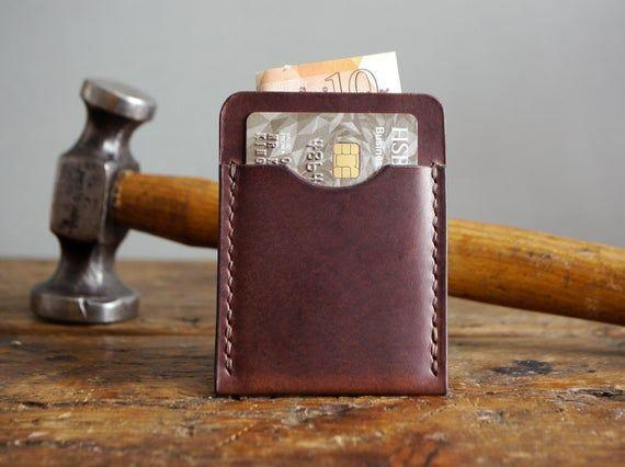 """<p><strong>KingsleyLeather</strong></p><p>etsy.com</p><p><strong>$95.53</strong></p><p><a href=""""https://go.redirectingat.com?id=74968X1596630&url=https%3A%2F%2Fwww.etsy.com%2Flisting%2F736857917%2Fdark-brown-leather-card-holder-slim&sref=https%3A%2F%2Fwww.womansday.com%2Frelationships%2Ffamily-friends%2Fg36467619%2Fbest-college-graduation-gifts%2F"""" rel=""""nofollow noopener"""" target=""""_blank"""" data-ylk=""""slk:Shop Now"""" class=""""link rapid-noclick-resp"""">Shop Now</a></p><p>A leather wallet is a true sign of sophistication, and this handmade one will last new grads a long time. It's a little on the pricey side, so maybe have a couple of family members or friends go in on this one.</p>"""