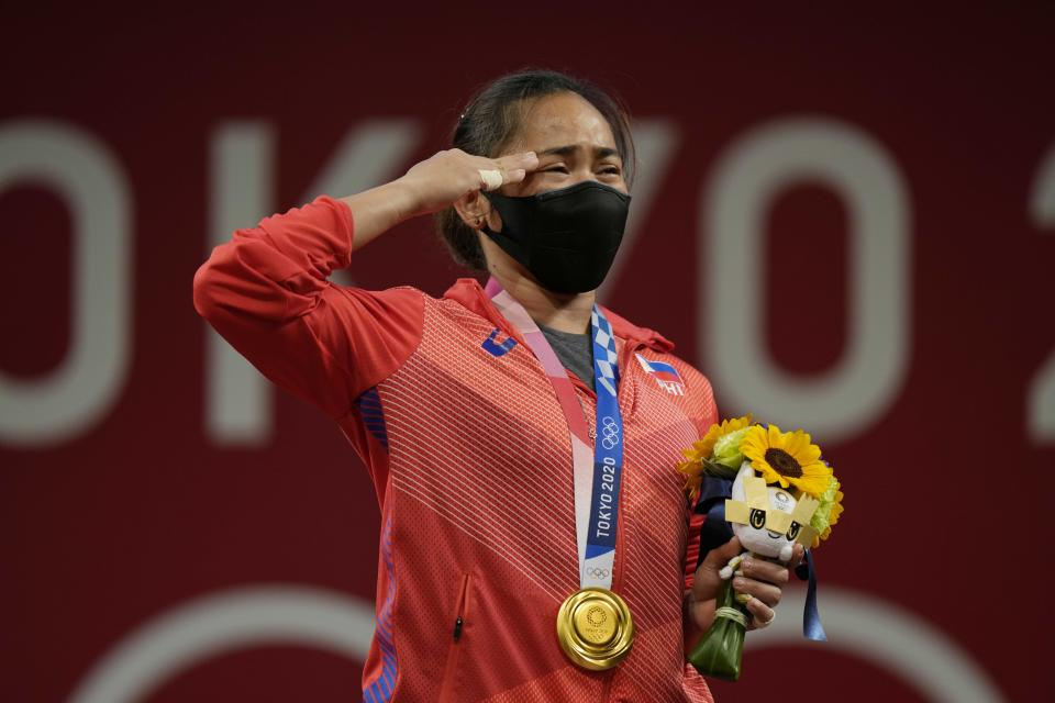 Hidilyn Diaz of Philippines gestures on the podium as she listen to the national anthem after winning the gold medal in the women's 55kg weightlifting event, at the 2020 Summer Olympics, Monday, July 26, 2021, in Tokyo, Japan. (AP Photo/Luca Bruno)