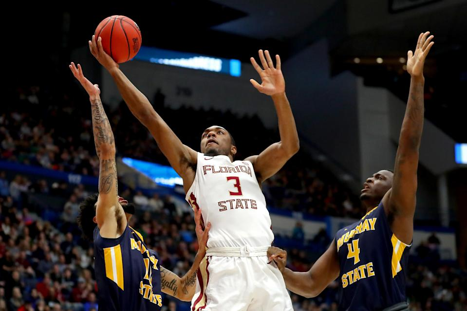 <p>Trent Forrest #3 of the Florida State Seminoles attempts a shot against Tevin Brown #10 and Brion Sanchious #4 of the Murray State Racers in the first half during the second round of the 2019 NCAA Men's Basketball Tournament at XL Center on March 23, 2019 in Hartford, Connecticut. (Photo by Maddie Meyer/Getty Images) </p>