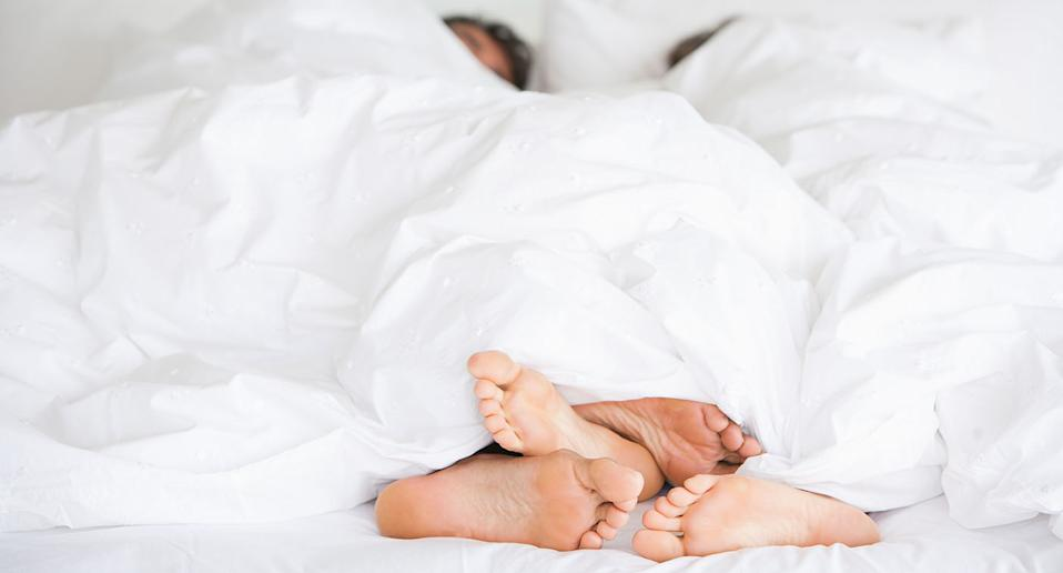 A couple lie in bed with only their feet showing from under the blanket.