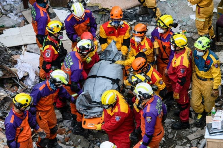 Rescue teams remove a body found in the Yun Tsui building