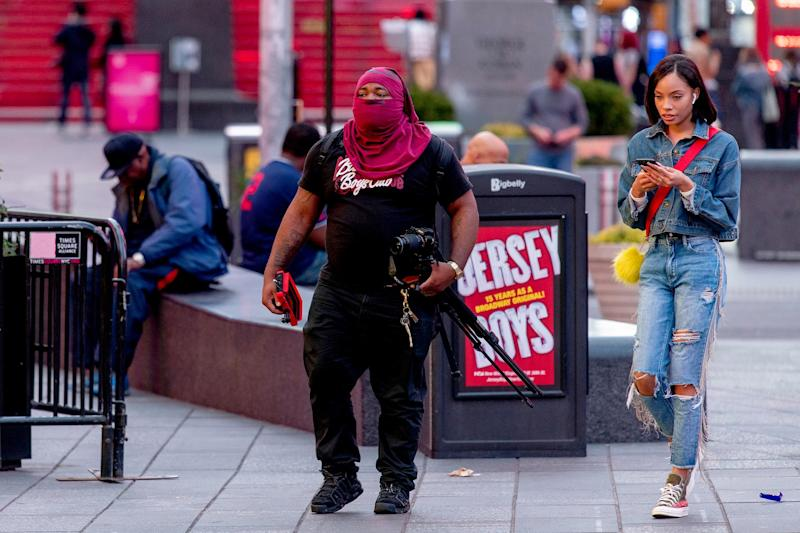UNITED STATES: A photographer covers his face in New York City's Times Square during the COVID-19 pandemic.