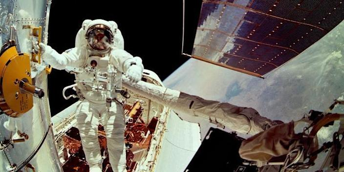 astronaut directs hubble space telescope in space suit above the earth
