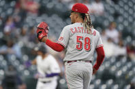 Cincinnati Reds starting pitcher Luis Castillo waits for a new ball after giving up a two-run home run to Colorado Rockies' Josh Fuentes during the first inning of a baseball game Thursday, May 13, 2021, in Denver. (AP Photo/David Zalubowski)