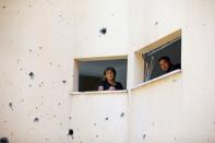 People look out from a building damaged after a rocket fired from the Gaza Strip last week landed nearby, in Petah Tikva