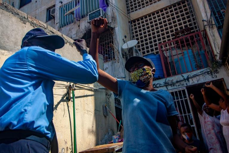A Luanda resident celebrates with a policeman after the Angolan National Director of Public Health lifted a two week virus quarantine order