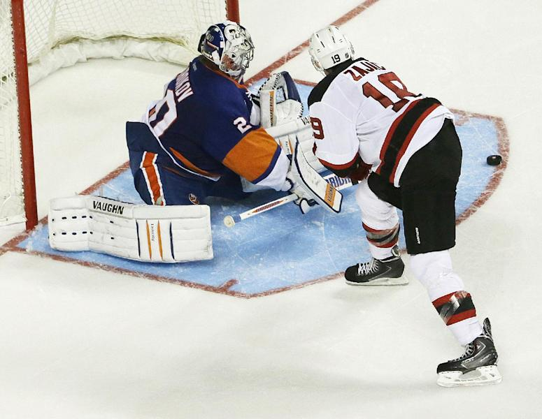 New York Islanders goalie Evgeni Nabokov, left, deflects a shot by New Jersey Devils' Travis Zajac during the third period of a preseason NHL hockey game, Saturday, Sept. 21, 2013, in New York. The Devils won 3-0. (AP Photo/Julio Cortez)
