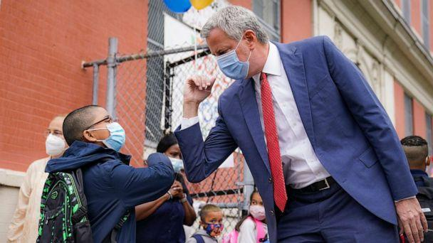 PHOTO: New York Mayor Bill de Blasio, right, greets students as they arrive for in-person classes outside Public School 188 The Island School, Sept. 29, 2020, in New York. (John Minchillo/AP)