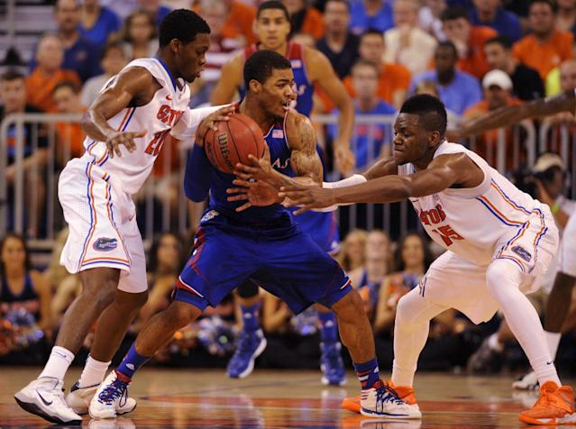 Univ. of Kansas guard Frank Mason (0) tries to keep the ball with Florida guard Michael Frazier II (20) and Florida forward Will Yeguete (15) try to get possession during the first half of an NCAA college basketball game Tuesday, Dec. 10, 2013 in Gainesville, Fla. (AP Photo/Phil Sandlin)